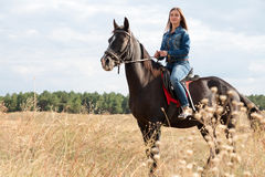 A young girl on a dark horse. A young girl in a denim suit on a dark horse Royalty Free Stock Image