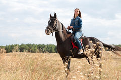 A young girl on a dark horse. A young girl in a denim suit on a dark horse Stock Images