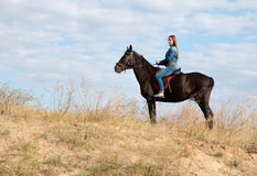 A young girl on a dark horse. A young girl in a denim suit on a dark horse Stock Photography