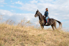 A young girl on a dark horse. Stock Images