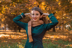Young girl in  dark jacket and scarf stands in autumn Park  raised her hands to  head Royalty Free Stock Image