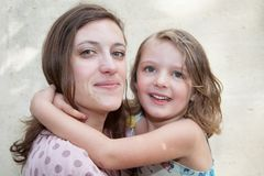 Young girl daughter hug mother outdoors. Cute young girl daughter hug mother outdoors stock photo