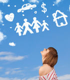 Young girl daydreaming with family and household clouds Royalty Free Stock Photos