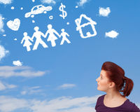 Young girl daydreaming with family and household clouds Royalty Free Stock Photo
