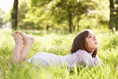 Young Girl Daydreaming Lying In Summer Field Stock Photos