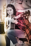 Young girl is deciding on acoustic guitar Stock Photo