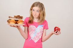Young girl deciding junk food or apple. On grey background Royalty Free Stock Photography