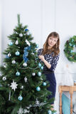 Young girl decorates Christmas tree Royalty Free Stock Photos
