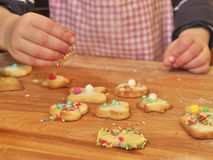 Young girl decorating butter cookies with sprinkles. Photo shows a kids hand decorating butter cookies with sprinkles Royalty Free Stock Images