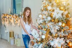 Young girl decorating Christmas tree at home royalty free stock images