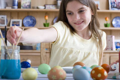 Young girl decorating Easter eggs Stock Photos