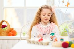 Young girl decorating Easter eggs at cozy home atmosphere. Beautiful young girl decorating Easter eggs at cozy home atmosphere Royalty Free Stock Photography