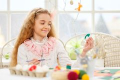 Young girl decorating Easter eggs at cozy home atmosphere. Stock Photo