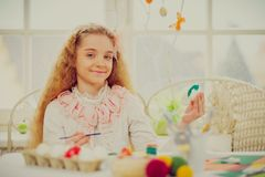 Young girl decorating Easter eggs at cozy home atmosphere. Royalty Free Stock Image