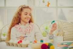 Young girl decorating Easter eggs at cozy home atmosphere. Beautiful young girl decorating Easter eggs at cozy home atmosphere Stock Images