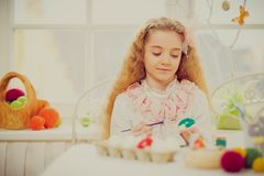 Young girl decorating Easter eggs at cozy home atmosphere. Beautiful young girl decorating Easter eggs at cozy home atmosphere Royalty Free Stock Image