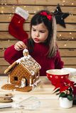 Young girl decorating gingerbread house royalty free stock photography