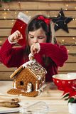 Young girl decorating gingerbread house. Photo of a young girl decorating a gingerbread house at home just before Christmas stock image