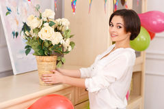 Young girl decorating her apartment for birthday. Decoration process. Young attractive girl is decorating her room with beautiful flowers Stock Photography