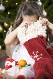 A young girl delving into a Christmas stocking Stock Images