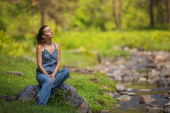 Young girl in a denim dress sits on stone near a stream in a forest Royalty Free Stock Image