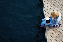 Young girl with a denim jacket, sitting with his legs dangling off the pier while using digital tablet Stock Images