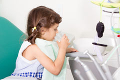 Young girl at dental clinic. Young girl rinses her teeth at dental clinic Stock Photo