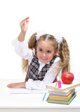 Young girl at a desk, hand raised Royalty Free Stock Image