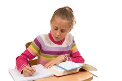 Young Girl at desk in school on white Stock Photos