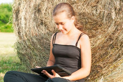 Young girl with  device siting close  to haystack Stock Photo