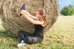 Young girl with  device siting close  to haystack Stock Photos