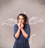 Young girl with devil horns and wings drawing Royalty Free Stock Photos