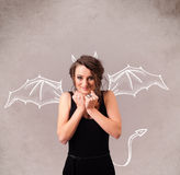 Young girl with devil horns and wings drawing Stock Photo