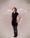 Young girl with devil horns and wings drawing Royalty Free Stock Photo