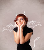 Young girl with devil horns and wings drawing Stock Image