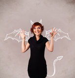 Young girl with devil horns and wings drawing Royalty Free Stock Photography