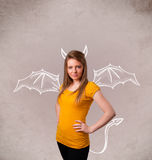 Young girl with devil horns and wings drawing Stock Photography