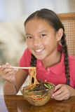Young girl in dining room eating chinese food Royalty Free Stock Photography