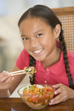 Young girl in dining room eating chinese food. Smiling Royalty Free Stock Photo