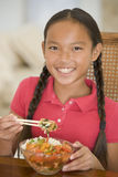 Young girl in dining room eating chinese food Stock Photography