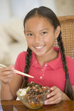 Young girl in dining room eating chinese food. Smiling Royalty Free Stock Images