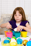 Young girl coloring Easter Eggs. A young girl dipping a hard boiled egg in blue dye, while in the process of coloring Easter Eggs. The egg is sitting on the Royalty Free Stock Images