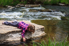 Young Girl Dipping Her Hand in the Water Stock Photo