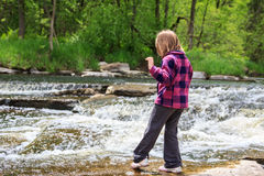 Young Girl Dipping Her Toe in the Water. Young girl playing by a stream in the woods. Tentatively dipping her toe in the water royalty free stock images