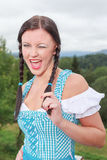 Young girl in dirndl with gaiety. Young Bavarian girl in a dirndl with much gaiety has fun stock photo