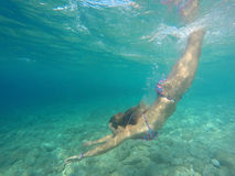 Young girl diving in blue sea Stock Photos