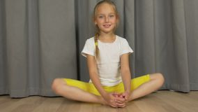 Young girl do yoga butterfly pose. White girl stretchin at living room indoors. stock video