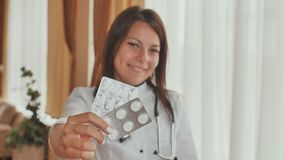 A young girl doctor demonstrates in the hands of a package of pills. A young girl doctor demonstrates in the hands of a package of pills stock video
