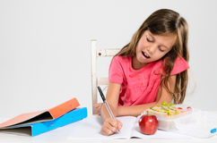 Young girl does her homework on table Stock Photo