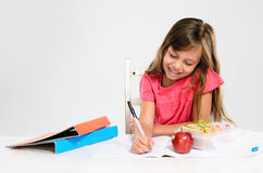 Young girl does her homework on table Royalty Free Stock Photo